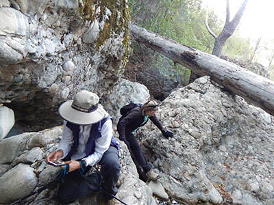 Photo of geographers inspecting boulders.