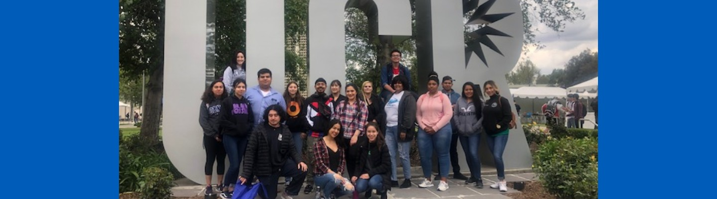 Transfer students in front of UC Riverside campus logo statue