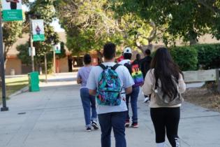 group of students with backpacks walking through campus