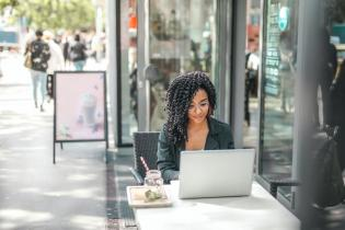 woman sitting outside cafe at bistro table using laptop