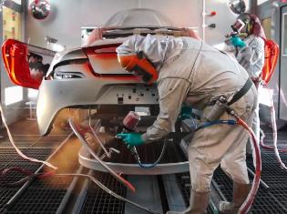 person painting a car in a professional paint booth setting