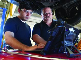 student and instructor working on a car