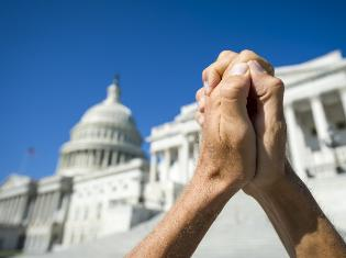 hands clasped together with image of white house in the background