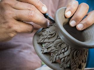 person carving design into wet clay