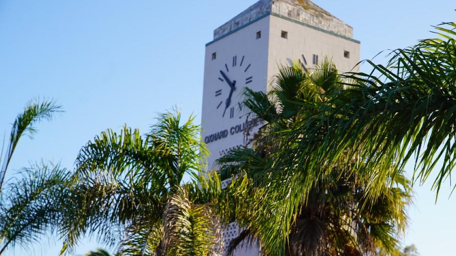Oxnard College clock tower with palm trees in the foreground